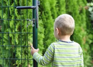 Junge im Garten vor Doppelstabmattenzaun Tor